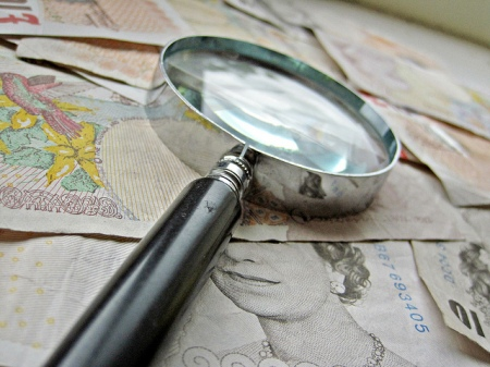 British paper money and magnigying glass