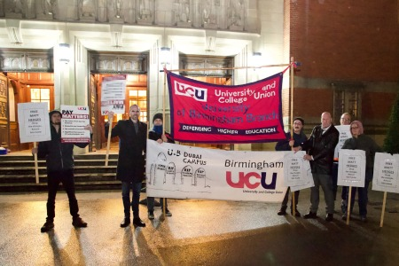 Members of University of Birmingham staff holding up banners and posters at the Matthew Hedges vigil