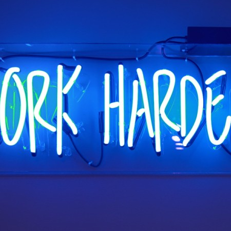 Neon sign showing the words 'work harder'