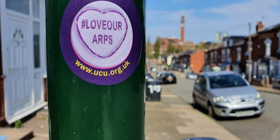 UCU 'Love our ARPS' sticker on a lamp post with street view in the background